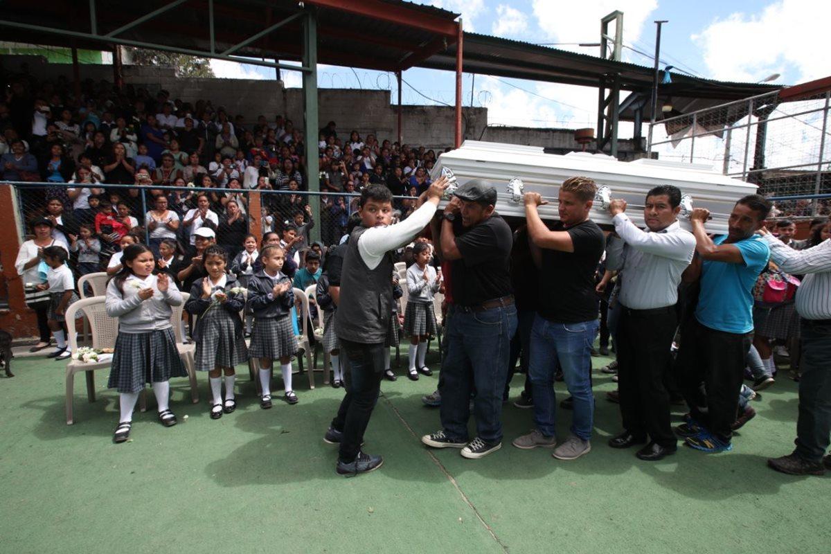 Padres y maestros cargan el ataúd de la seño Gaby durante el homenaje en su escuela. (Foto Prensa Libre: Paulo Raquec)