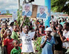 Partidarios del presidente de Burundi, Pierre Nkurunziza sostienen fotografías de él, durante su llegada a la capital, Bujumbura, Burund (Foto Prensa Libre:AP).