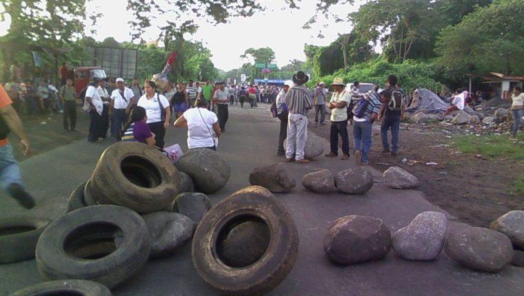 Campesinos utilizan piedras y llantas para impedir el paso de vehículos en Santa Cruz Muluá, Retalhuleu. (Foto Prensa Libre: Jorge Tizol)