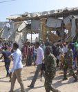 Soldados somalíes y curiosos se reúnen en el lugar de una explosión.(Foto Prensa Libre:EFE).