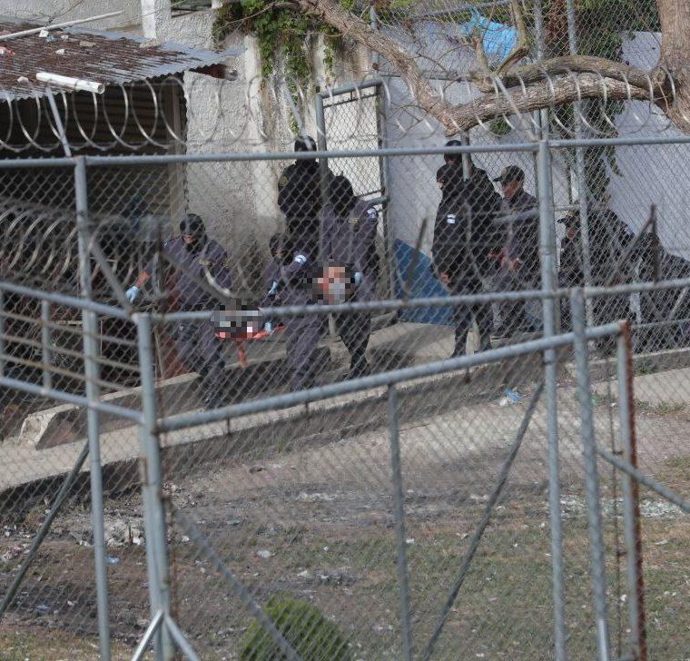 Guardias penitenciarios extraen uno de los cuerpos de los pandilleros asesinados. (Foto Prensa Libre: Estuardo Paredes).