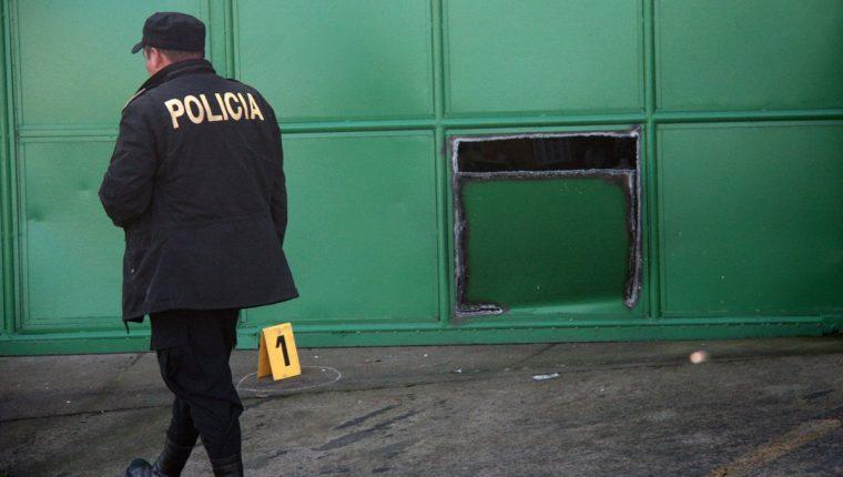 Un agente de la PNC resguarda el inmueble en el que desconocidos entraron para robar. (Foto Prensa Libre: Carlos Ventura)