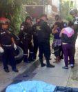 Agentes de la PNC conversan con vecinos de la colonia Villalobos 1 en el lugar del crimen. (Foto Prensa Libre: CBM)