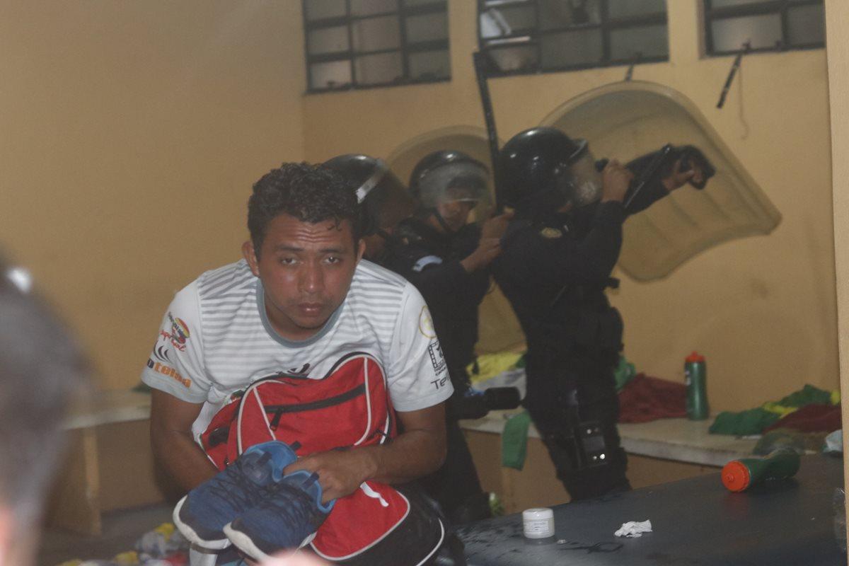 Josualdo Rodríguez, portero suplente de Guastatoya, sale agachado con sus pertenencias mientras apedreaban el camerino.