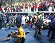 La caída de la barrera provocó que varios aficionados cayeran en una de las bancas. (Foto Prensa Libre: AFP)