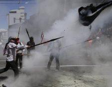 Manifestantes lanzan objetos a la Policía, en Quito. (Foto Prensa Libre: AP).