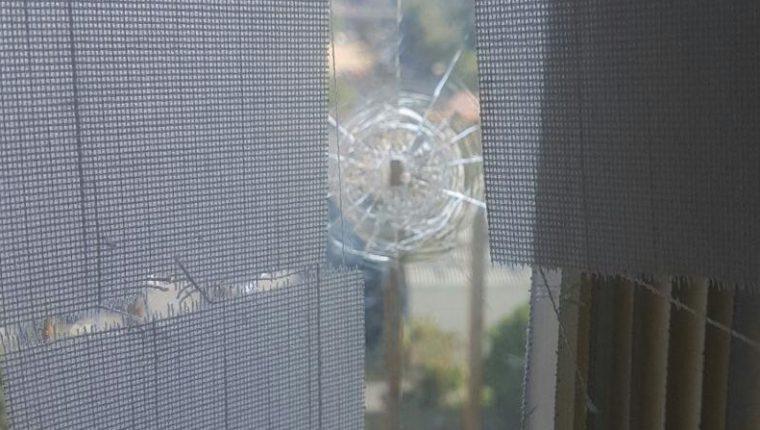 Una de las ventanas ubicadas en la redacción de Canal Antigua resultó con daños debido al proyectil de arma de fuego. (Foto Prensa Libre:)