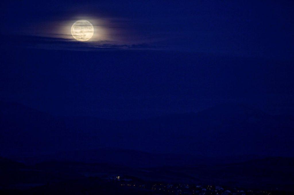 La primera luna llena del invierno astronómico, que comenzó la pasada noche, se eleva sobre la llanada Alavesa y el monte Aratz,  vista desde la cima del monte Olarizu, en Vitoria, al norte de España.