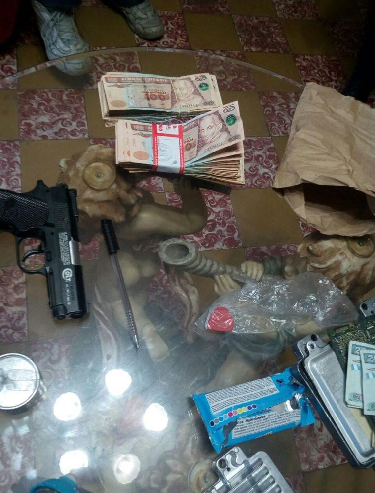 Dinero y un arma localizada durante allanamientos contra extorsionistas en Mixco. (Foto Prensa Libre: PNC)