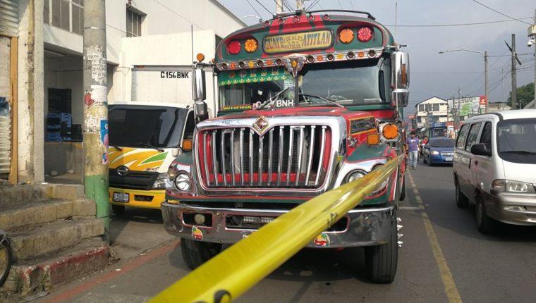 Agentes de la PNC resguardan autobús en el que murió un ayudante, en Amatitlán. (Foto Prensa Libre: Estuardo Paredes)