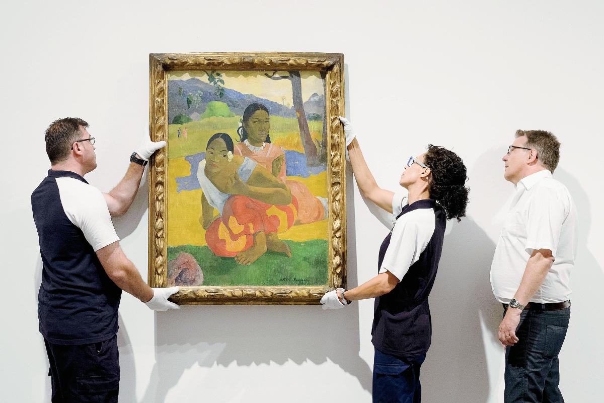 """Dos empleados del Museo Reina Sofía instalan el cuadro de Paul Gauguin's """"Nafea Ipoipo faa"""", la obra más cara vendida del mundo. (Foto Prensa Libre, AFP)"""