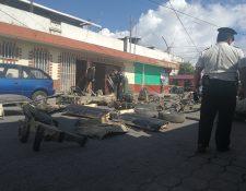 Un agente de la PNC resguarda las piezas de automóviles que fueron decomisadas. (Foto Prensa Libre: Fred Rivera).