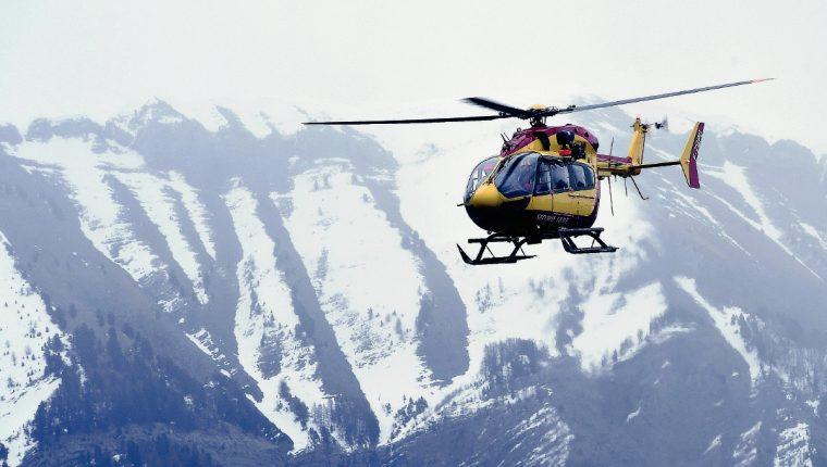 Un helicóptero sobrevuela los Alpes franceses, en busca de sobrevivientes. Los equipos de rescate suspendieron labores debido a la falta de visibilidad. (Foto Prensa Libre: AFP).
