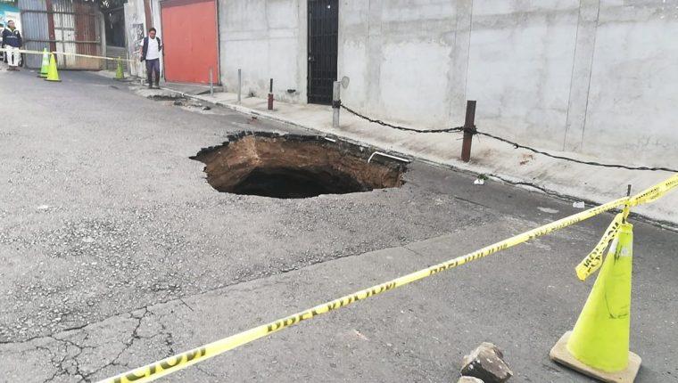 Vecinos evitan caminar cerca del agujero que se formó en la vía principal de la colonia Pablo Sexto, en la zona 7 de Mixco. (Foto Prensa Libre: Edwin Pitán)