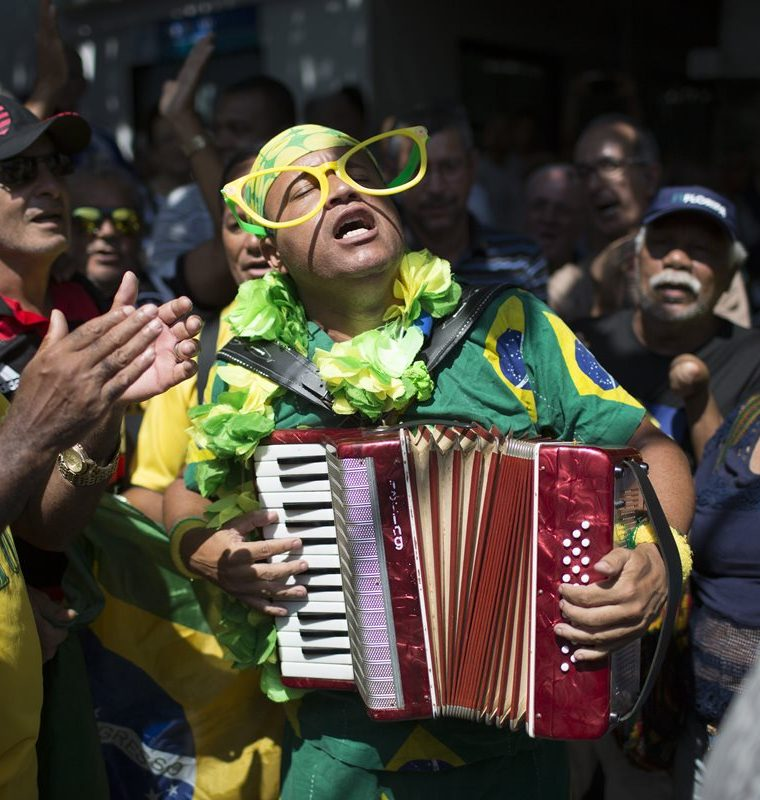 A fan performs during the burial of soccer great Carlos Alberto Torres at a cemetery in Rio de Janeiro, Brazil, Wednesday, Oct. 26, 2016. Torres, the captain of Brazil's World Cup-winning team in 1970 and scorer of one of the sport's most memorable goals, died on Tuesday. He was 72 and died of after a heart attack at his home in Rio de Janeiro. (AP Photo/Leo Correa)