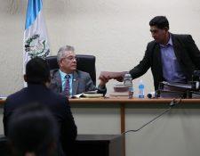 Momento en que el juez Miguel Ángel Gálvez entrega fotografías de la vivienda de Juan Carlos Monzón que fue violentada por sujetos armados. (Foto Prensa Libre: Paulo Raquec)