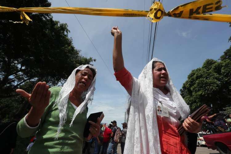Mujeres oran en las afueras del área cero para pedir por las personas que trabajan en el lugar y por las almas de los fallecidos.