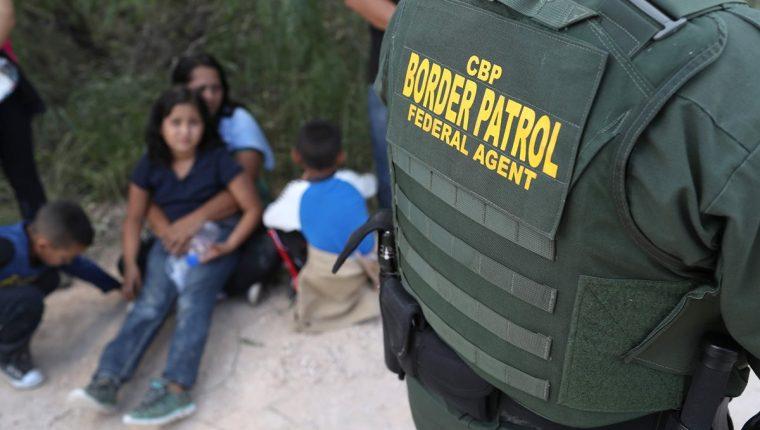 Un guardia fronterizo vigila a una familia, recién detenida en la frontera sur de EE. UU. (Foto Prensa Libre: AFP)