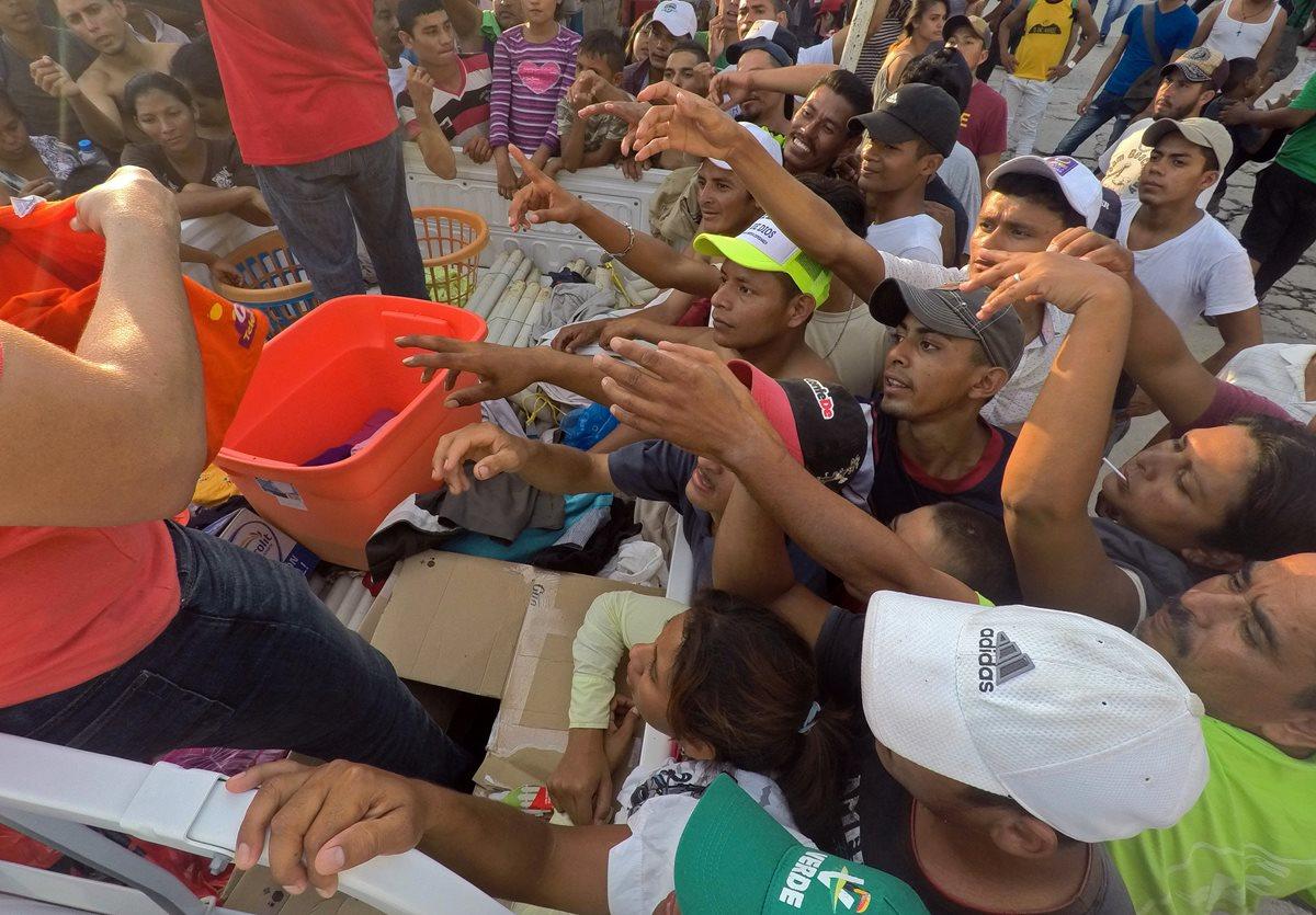 Migrantes hondureños reciben alimentos hoy en el municipio de Pijijiapan, en el estado de Chiapas, México. (Foto Prensa Libre: EFE)