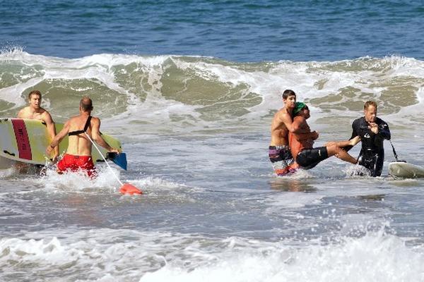 Dos hombres ayudan en el rescate del hombre herido por el tiburón en California (Foto Prensa Libre: AP).