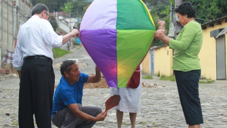 Marco Antonio Chacón Chinchilla (azul) es uno de los últimos artesanos que se dedica a la confección y elevación de globos de colores de papel de china, una tradición casi por completo olvidada. (Foto Prensa Libre: Estuardo Paredes)