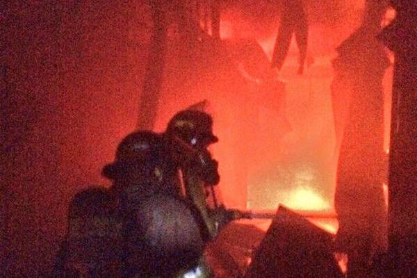 Socorristas combaten las llamas entre los locales. (Foto Prensa Libre: CBM)