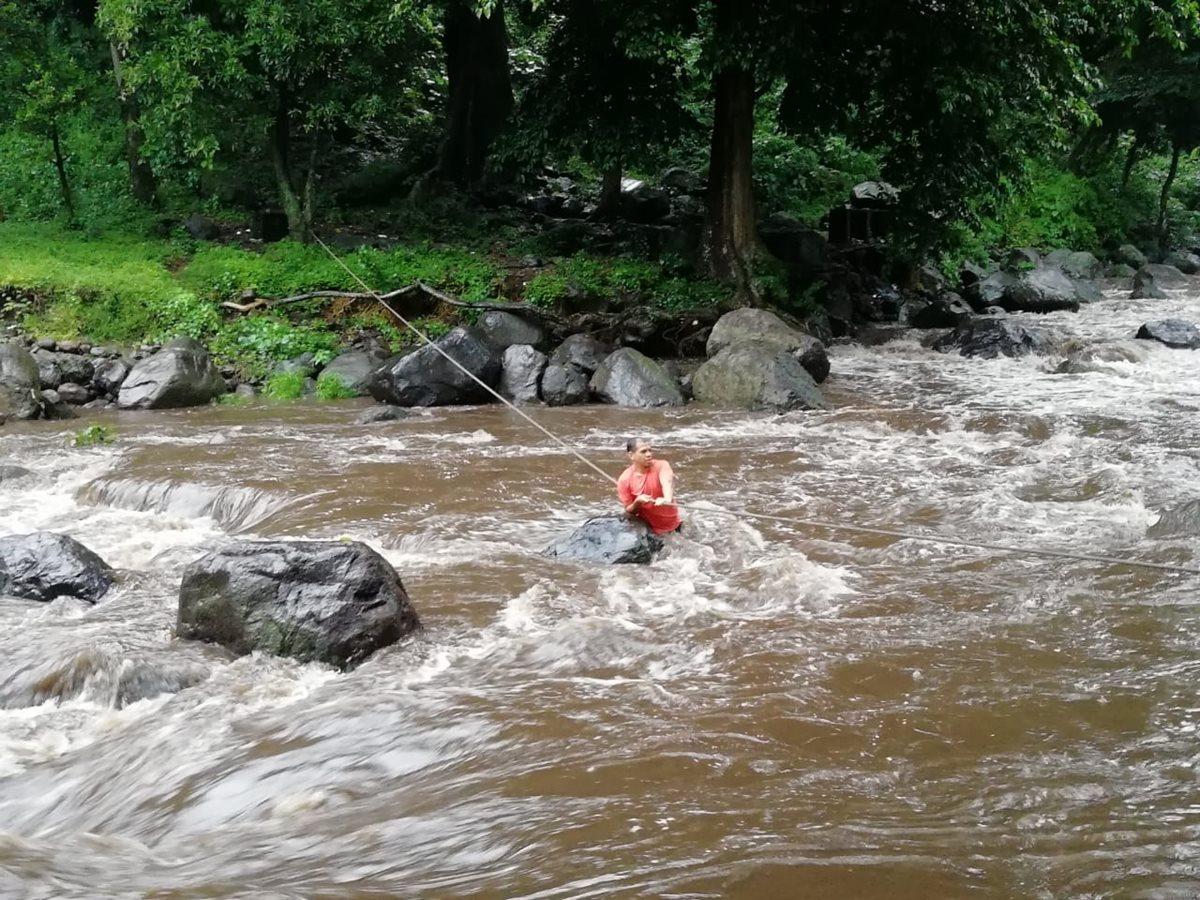 Uno de los turistas cruza el río Cantil, en Escuintla, donde los Bomberos Voluntarios colocaron cables para facilitar el rescate. (Foto Prensa Libre: Carlos Paredes)