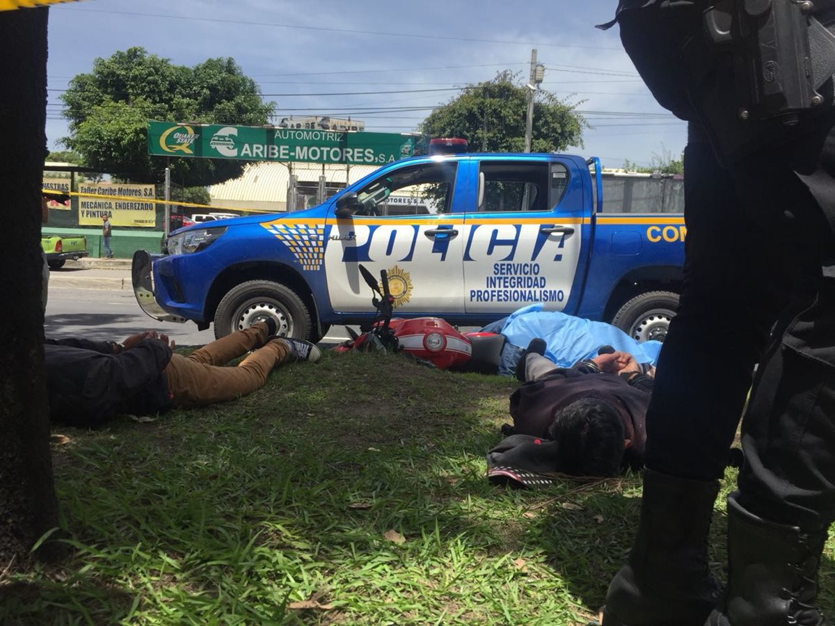 Policía resguarda a los dos supuestos menores capturados; al fondo, la moto y la persona fallecida. (Foto: Cortesía)