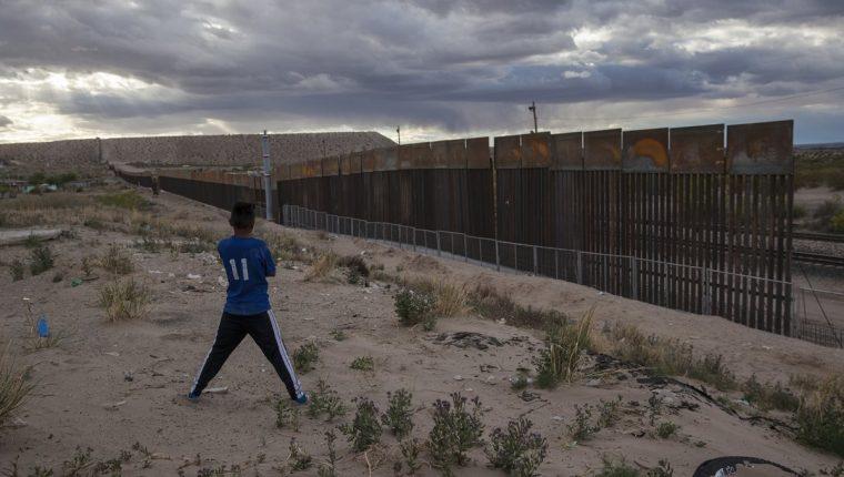 Un joven observa el muro en Ciudad Juárez, México. (Foto Prensa Libre: AP)