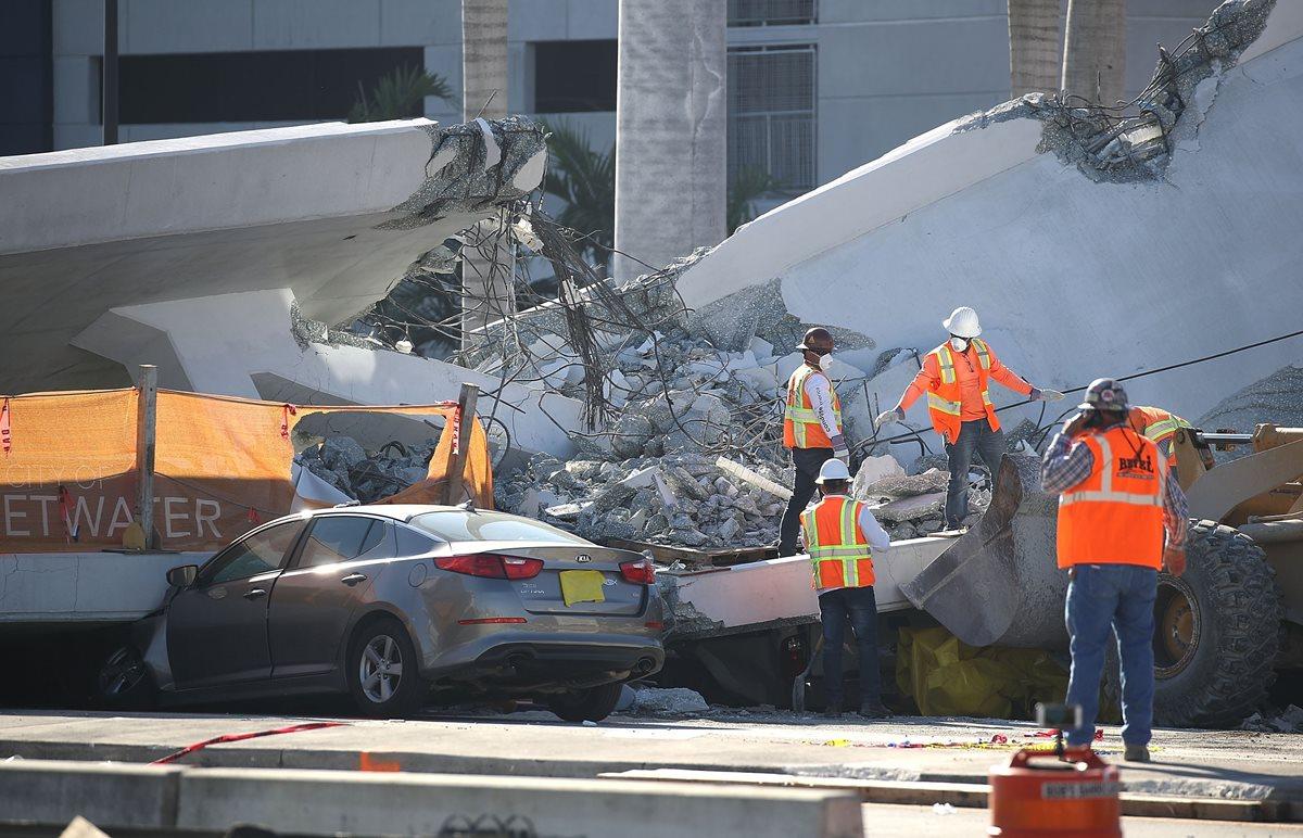 Un grupo de trabajadores, policías y integrantes de la Junta Nacional de Seguridad del Transporte investigan la escena del puente peatonal se derrumbó. (AFP).