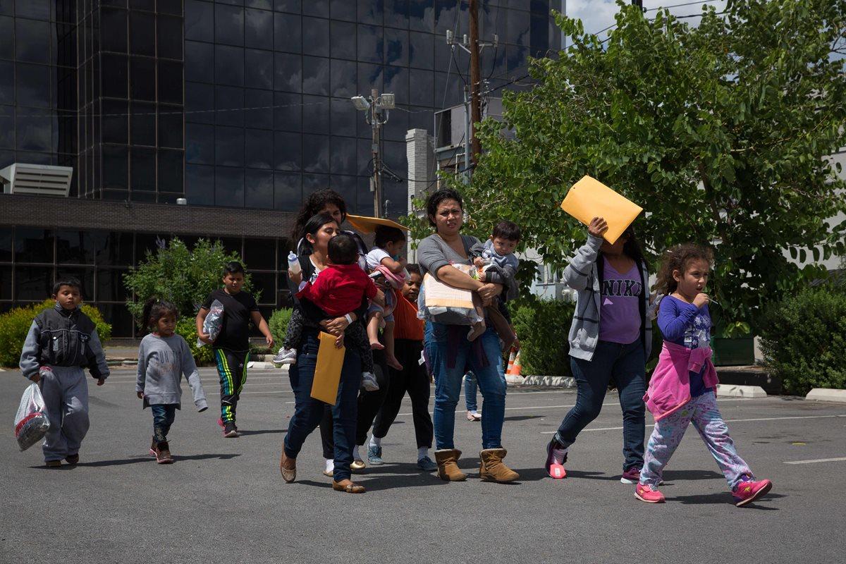 Un grupo de inmigrantes centroamericanos caminan después de ser dejados en una estación de autobuses poco después de ser liberados en McAllen, Texas. (Foto Prensa Libre:AFP)