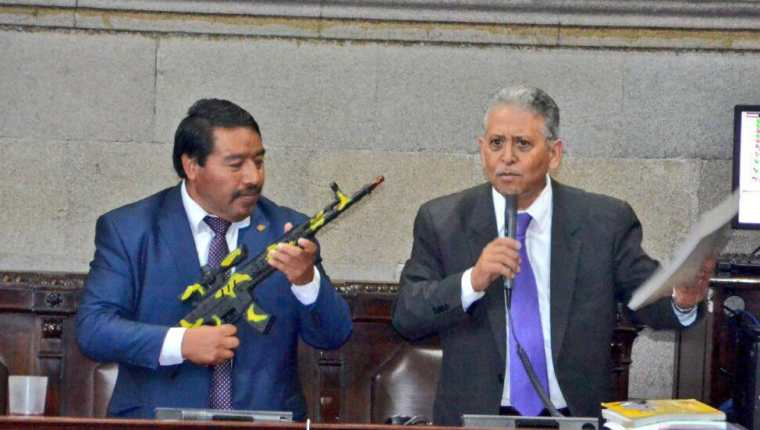 El diputado Pedro Méndez Carreto, sostiene un fusil de juguete mientras su colega Ovidio Monzón, discute sobre la necesidad de asignar más presupuesto a la Educación y no al Ejército. (Foto Prensa Libre: José Castro)