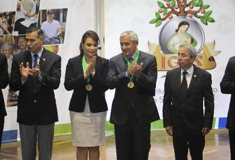 La vicepresidenta Roxana Baldetti  y el mandatario Otto Pérez aplauden al ser condecorados por Juan Rodríguez,  exsecretario  del presidente —izquierda—.