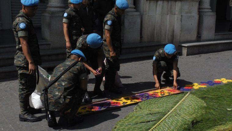 Miembros del ejército pertenecientes a las Fuerzas de Paz de la ONU elaboran una alfombra frente al Portal de Comercio. (Foto: Néstor Galicia)