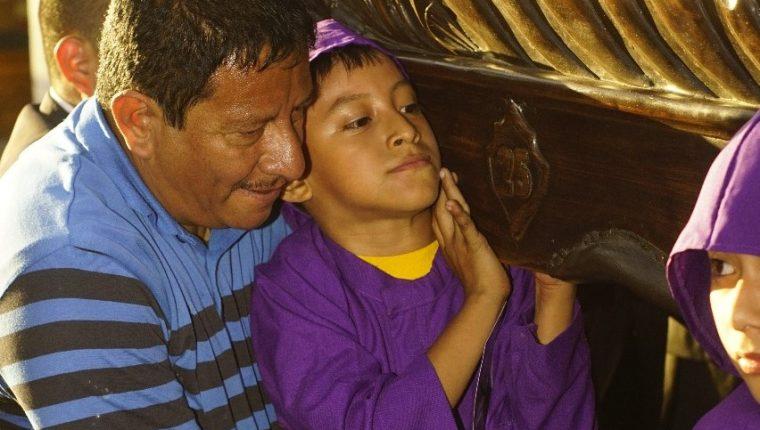 Marvin Leonel Hernández carga a su hijo Natanael José David Hernández para que participe en procesión infantil en Antigua Guatemala. (Foto Prensa Libre: Roberto Masaya).