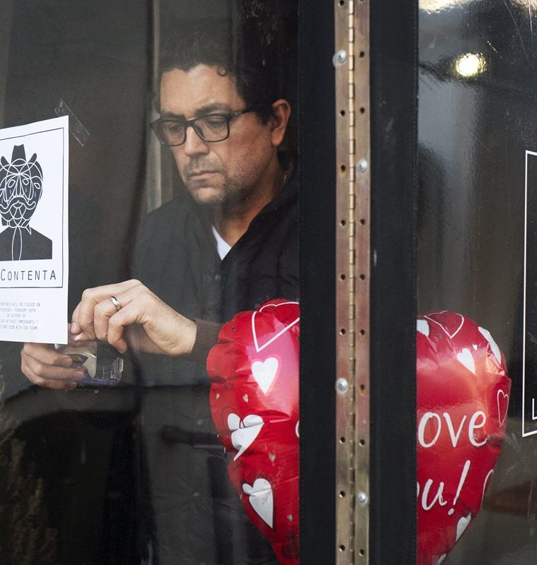 Luis Arce Mota, the chef and co-owner of La Contenta, posts a flyer in the window announcing the closure of his restaurant for the day, Thursday, Feb. 16, 2017, in New York. Mota, from Mexico, is now a U.S. citizen. Immigrants around the U.S. stayed home from work and school Thursday to demonstrate how important they are to America's economy and its way of life, and many businesses closed in solidarity. (AP Photo/Mark Lennihan)