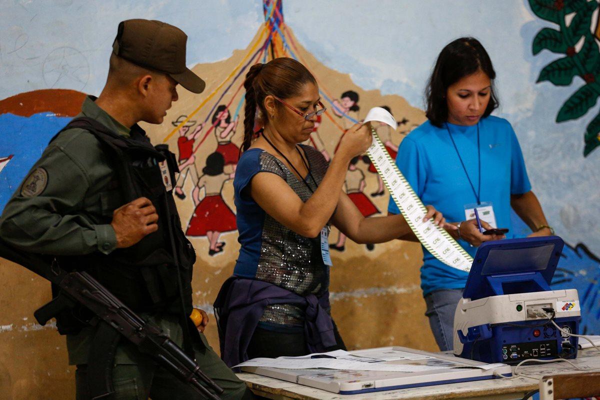 Un soldado supervisa el conteo de votos en un centro de votación de Caracas. (Foto Prensa Libre: EFE)