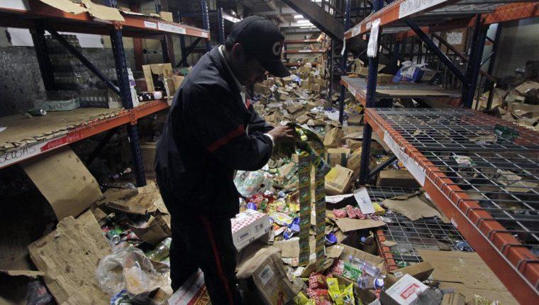 Un guardia de seguridad muestra las mercancías del supermercado después de los saqueos durante las protestas. (Foto Prensa Libre: AFP )