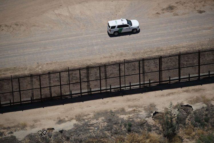 Un automóvil de la policía fronteriza vigila cerca del campamento para niños.