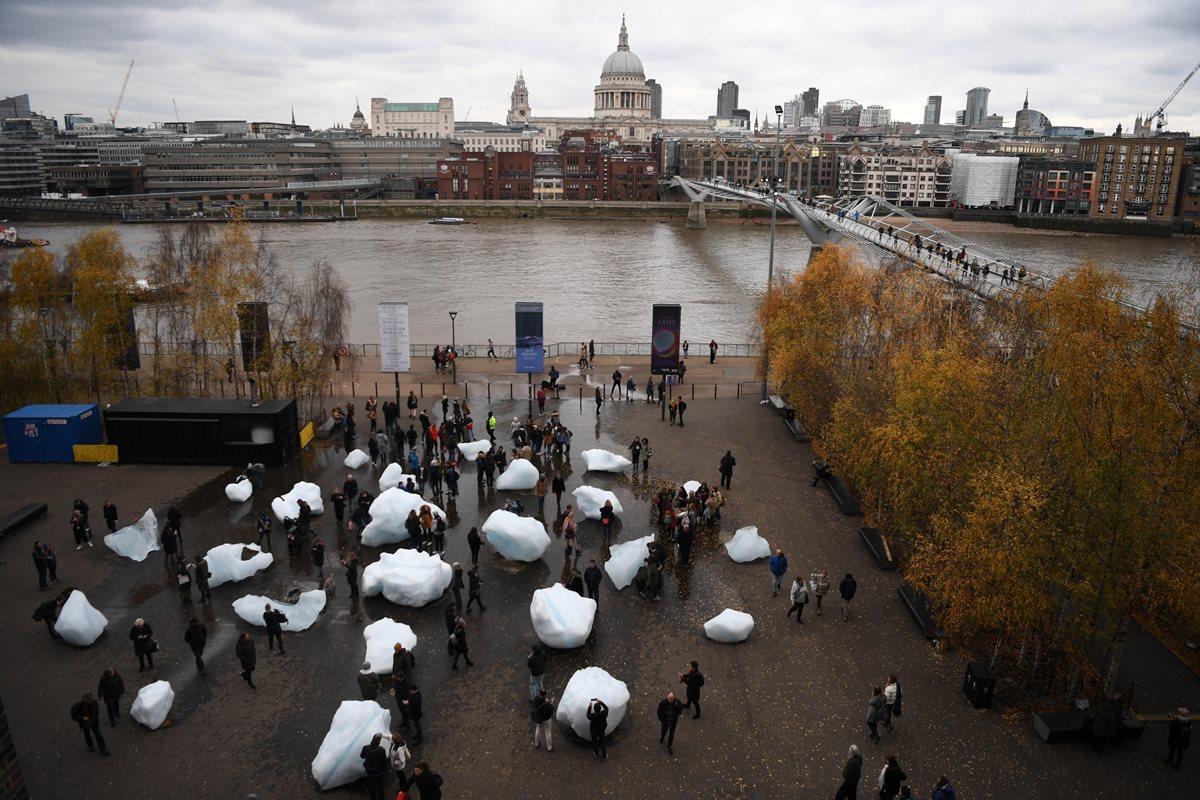 """Visitantes observan la obre """"Ice Watch"""" (lit.Reloj de hielo) de los artistas Minik Rosing y Olafur Eliasson a las afueras del Museo Nacional Británico de Arte Moderno en Londres, Reino Unido.Bloques de hielo de entre 1.5 y media y 6 toneladas de peso fueron traídos de Groenlandia para concienciar sobre los efectos del cambio climático. (Foto Prensa Libre: EFE)"""