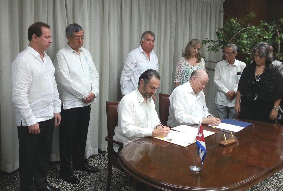 El ministro de Economía, Acisclo Valladares Urruela y el ministro de Comercio Exterior y la Inversión Extranjera de Cuba, Rodrigo Malmierca firman el acuerdo. Observa el vicepresidente de Guatemala Jafeth Cabrera. (Foto, Prensa Libre: Mineco).