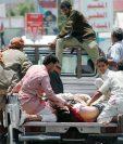 Hombres trasladan a heridos por los bombardeos de los países aliados perpetrados en la capital de Yemen. (Foto Prensa Libre: AFP).