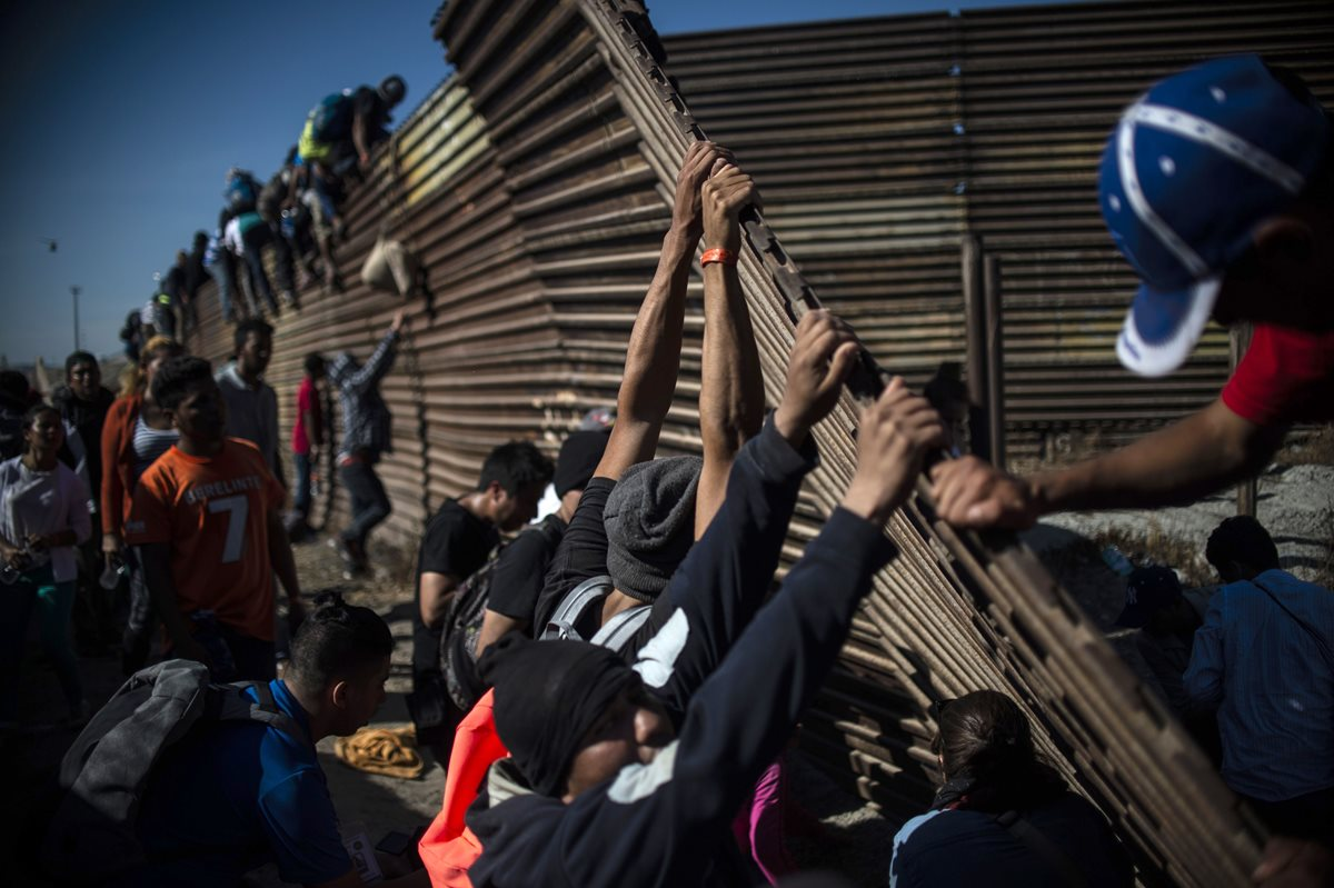 Un grupo de migrantes centroamericanos, principalmente hondureños, trepan la frontera entre México y Estados Unidos mientras otros intentan derribarla