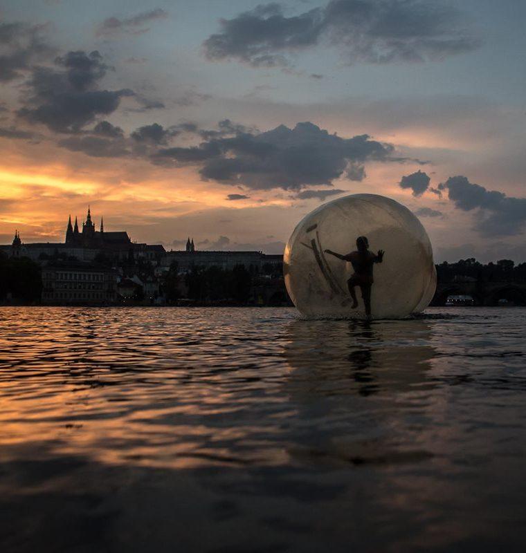 Un niño juega dentro de una pelota de plástico gigante, llamada zorb, durante el atardecer en una tarde calurosa de verano en Praga. (Foto Prensa Libre: EFE)