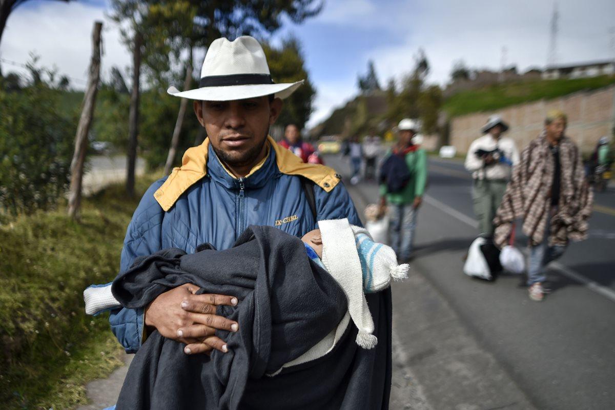 Familias venezolanas son captadas cuando caminan en la carretera Panamericana, Colombia, en su travesía hacia Perú. (Foto Prensa Libre: AFP)
