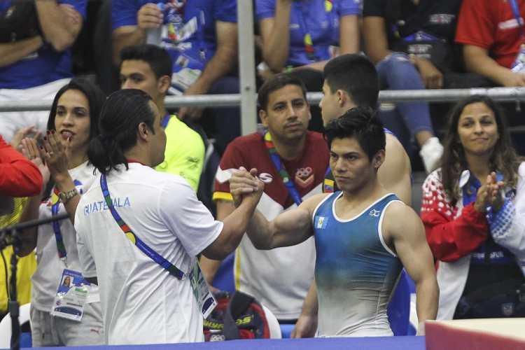Jorge Vega y su entrenador Rodman Murga, después de su rutina de piso, en Barranquilla 2018. (Foto Prensa Libre: Cortesía ACD)