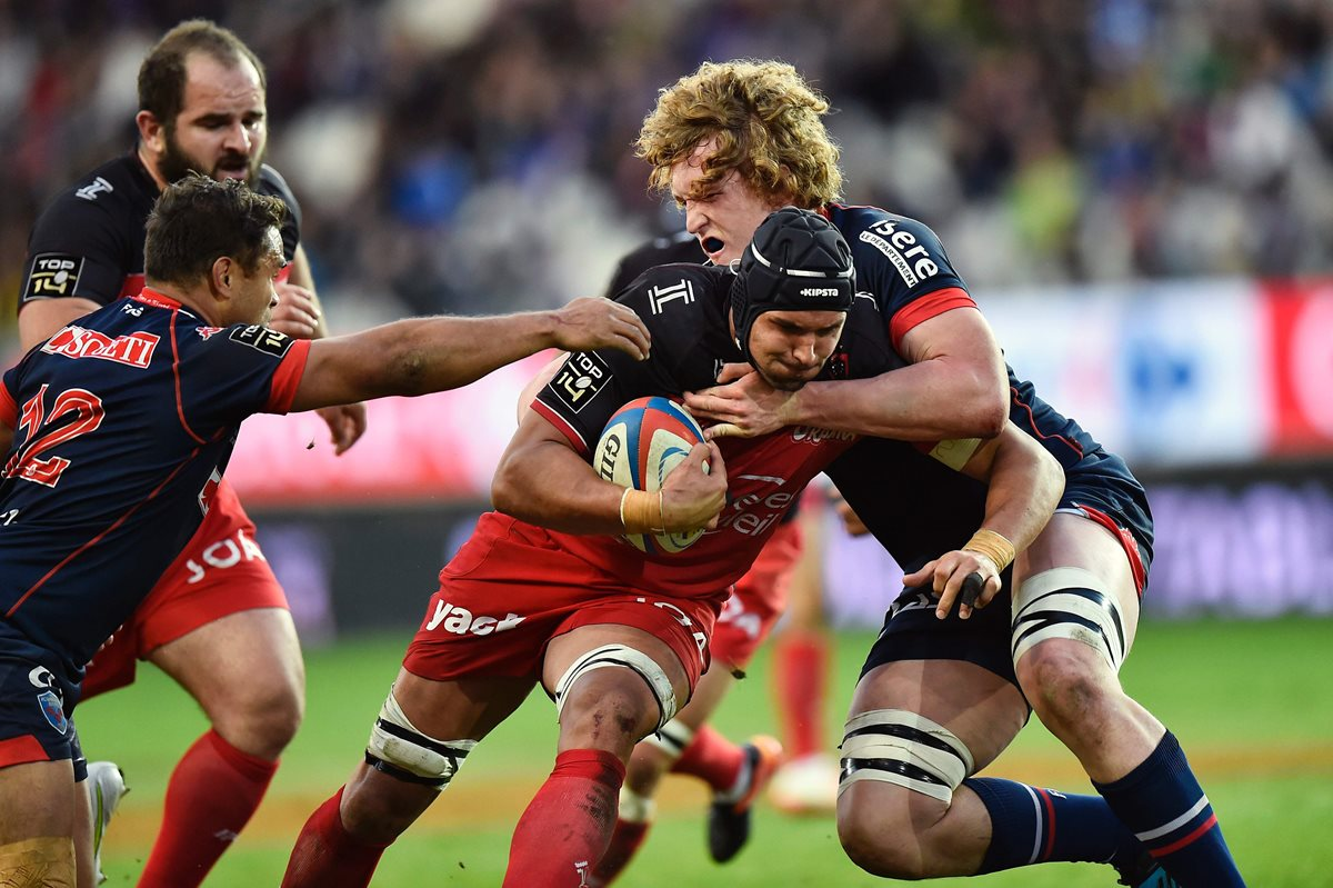 Toulon's South African lock Juandre Kruger (C) is challenged by Grenoble's French lock Thomas Jolmes (R) and Grenoble's New Zealander centre Nigel Hunt (L) during the French Top 14 rugby union match between FC Grenoble (FCG) and RC Toulon (RCT) on March 19, 2017 at the Stade des Alpes Stadium in Grenoble, central-eastern France. / AFP PHOTO / ROMAIN LAFABREGUE