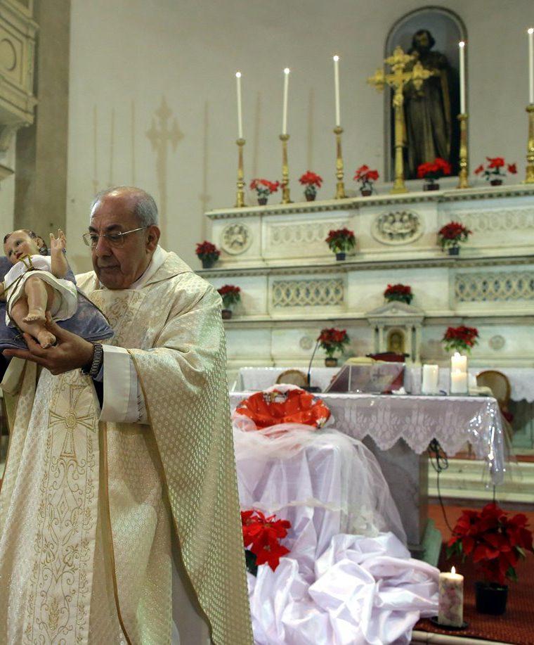 El sacerdote Farah porta la estatua de Jesus durante la Misa de Gallo en la Iglesia de San José en El Cairo, Egipto. (EFE).
