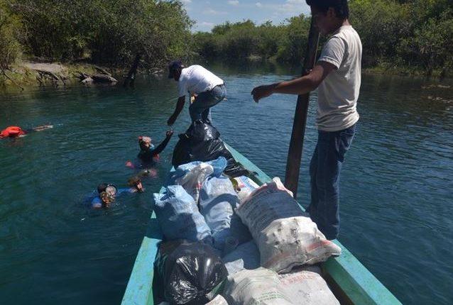 Lancheros transportan en lancha parte de la basura encontrada en la laguna Cráter Azul. (Foto Prensa Libre: Cortesía).