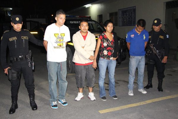 Policías custodian a los cuatro detenidos que huyeron en un taxi con armas y municiones. (Foto Prensa Libre: PNC)